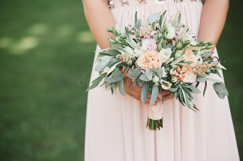 The bride in an elegant wedding dress holds a beautiful bouquet of different flowers and green leaves. Wedding theme stock photo