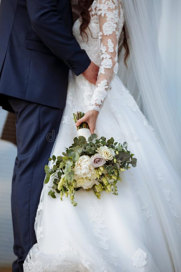 The bride in an elegant wedding dress holds a beautiful bouquet of different flowers and green leaves. Wedding theme.  stock photo