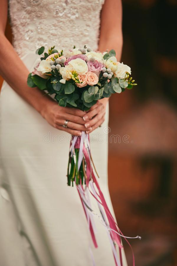 The bride in an elegant wedding dress holds a beautiful bouquet of different flowers and green leaves. Wedding theme stock photos