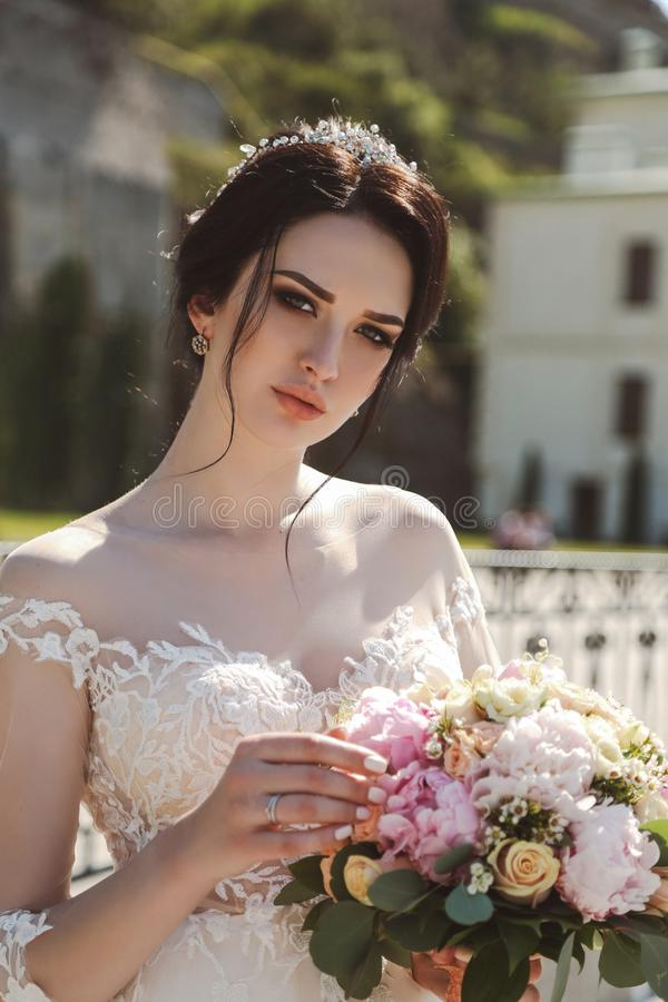 bride in elegant wedding dress posing outdoor with tender bouquet of flowers stock images
