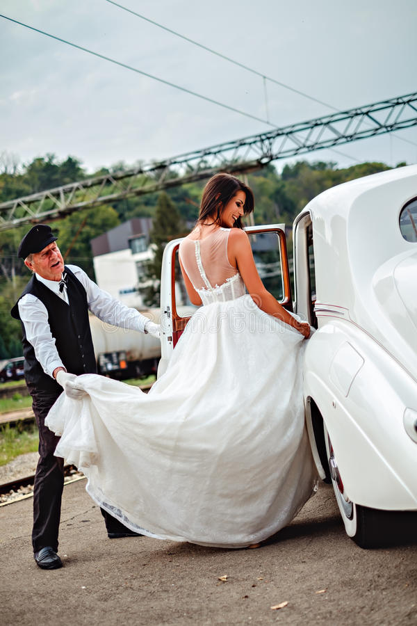 Bride entering classic car and driver holding dress royalty free stock images