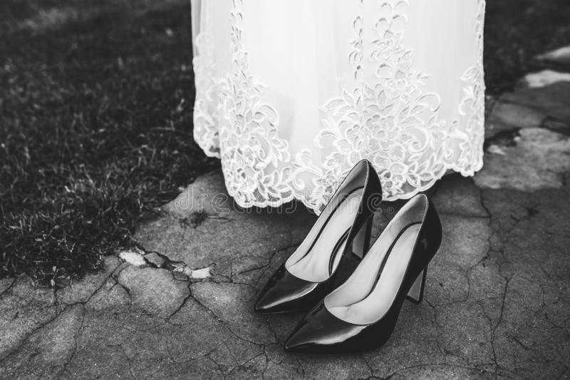Bride fitting shoes on her wedding day. Black and white royalty free stock photography