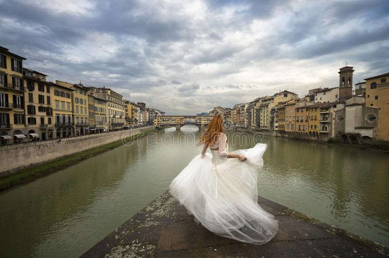 Bride in Florence. Ponte vecchio old bridge. Florence, Italy. Florence. Young bride on the bridge. With background the Arno river and the famous Ponte Vecchio stock photography
