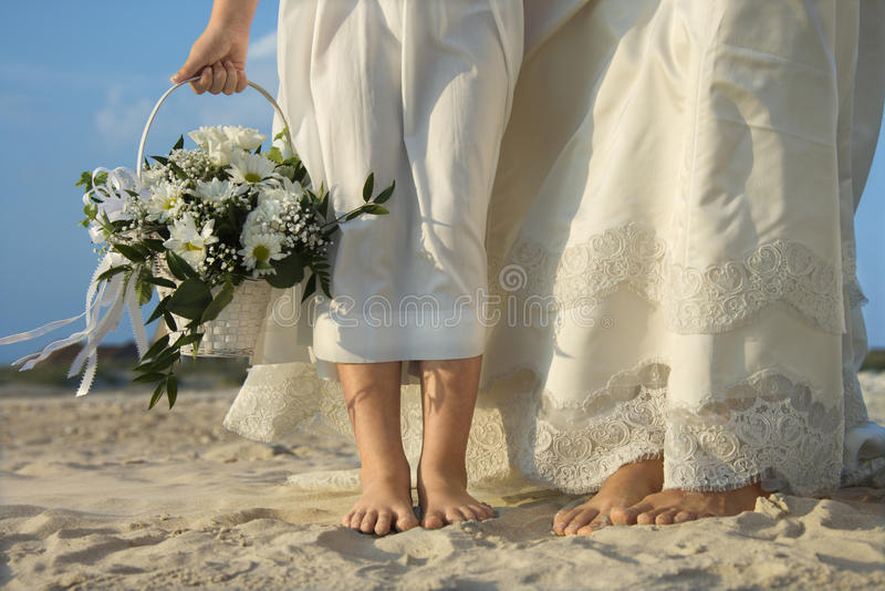 Bride And Flower Girl On Beach Royalty Free Stock Images