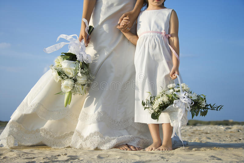 Bride and Flower Girl on Beach stock images