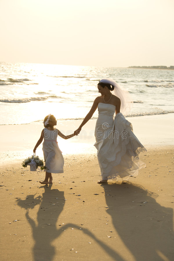 Bride and flower girl walking royalty free stock photo