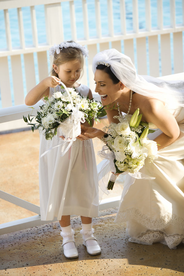 Bride and flowergirl. Caucasian mid-adult bride kneeling next to flower girl admiring her flowers stock image