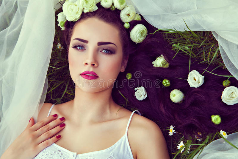 Bride with flowers in hair and veil lying on grass. Bride with natural flowers in hair lying on grass stock image