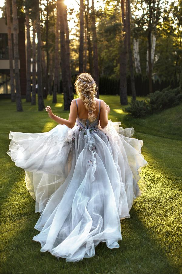 The bride in a flying dress in the evening sun stock photography