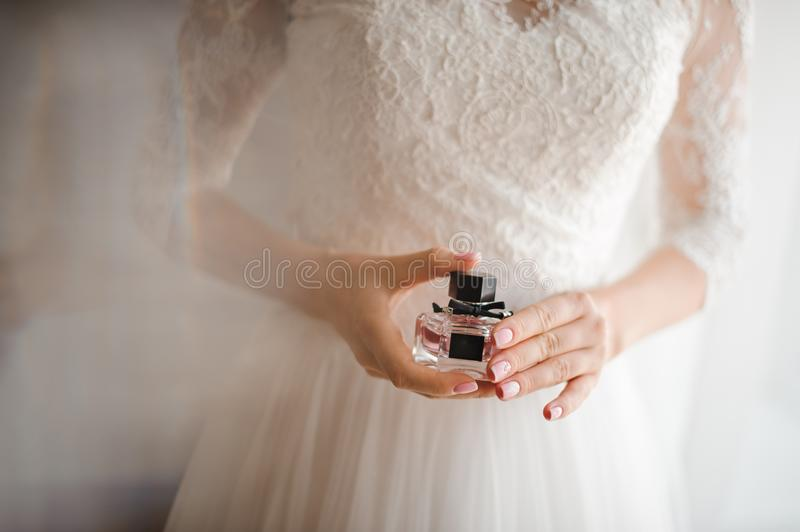 Bride with French manicure holds a bottle of perfume. Bride in a white dress with a pastel French manicure holds in her hand a bottle of perfume stock photography