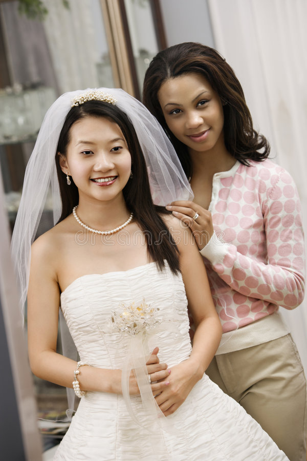 Bride and friend. Asian bride and African-American friend admiring dress in mirror stock photography
