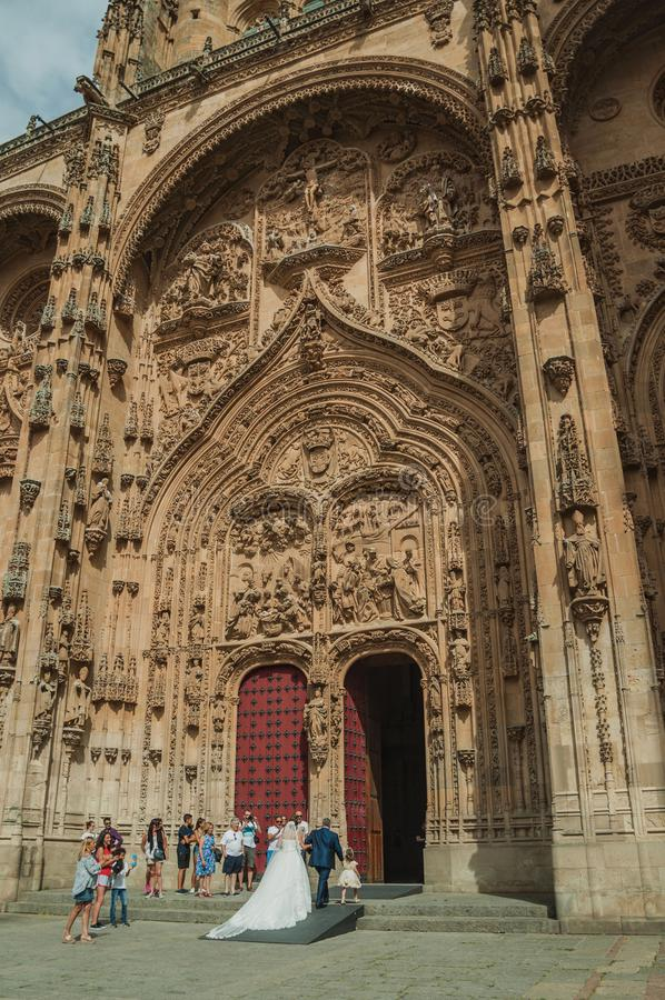 Bride on the front door of the New Cathedral at Salamanca. Salamanca, Spain - July 21, 2018. Bride coming through the front door of the finely ornate New royalty free stock photo