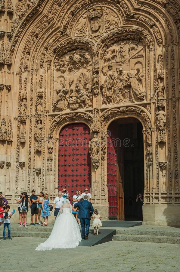 Bride on the front door of the New Cathedral at Salamanca. Salamanca, Spain - July 21, 2018. Bride coming through the front door of the finely ornate New stock photos