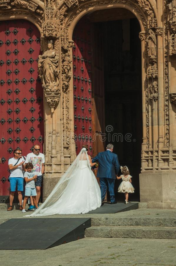 Bride on the front door of the New Cathedral at Salamanca. Salamanca, Spain - July 21, 2018. Bride coming through the front door of the finely ornate New royalty free stock images