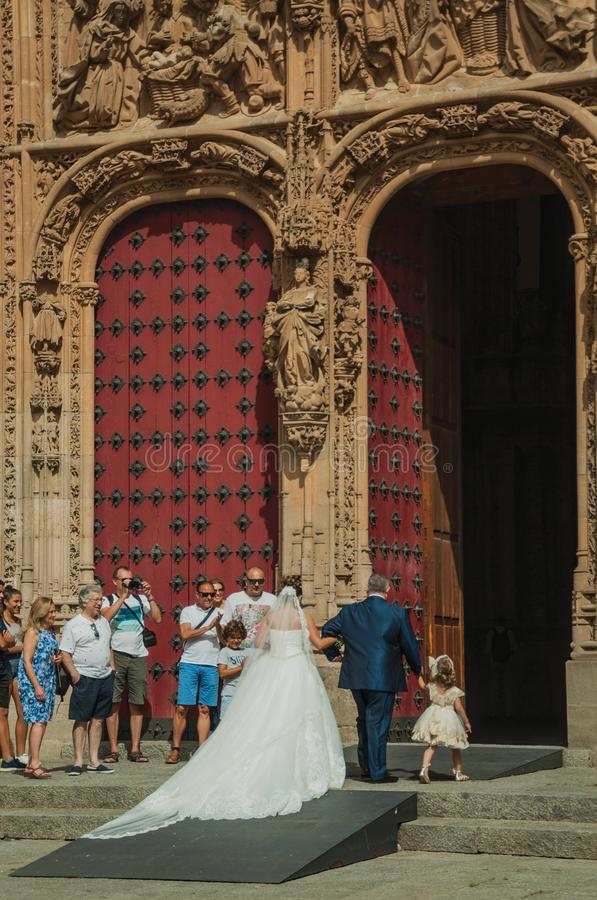 Bride on the front door of the New Cathedral at Salamanca. Salamanca, Spain - July 21, 2018. Bride coming through the front door of the finely ornate New stock photography