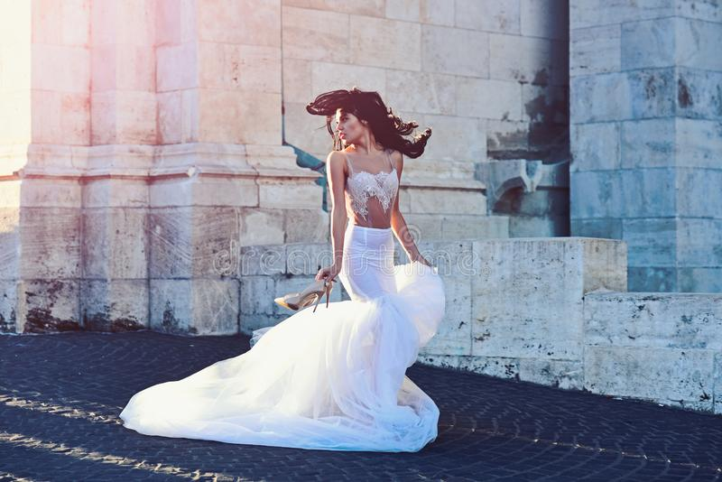 Bride girl at wedding ceremony in castle. Woman at stone ancient tower in summer. Sexy girl in white dress with stylish. Hair. Wedding fashion and beauty salon stock image