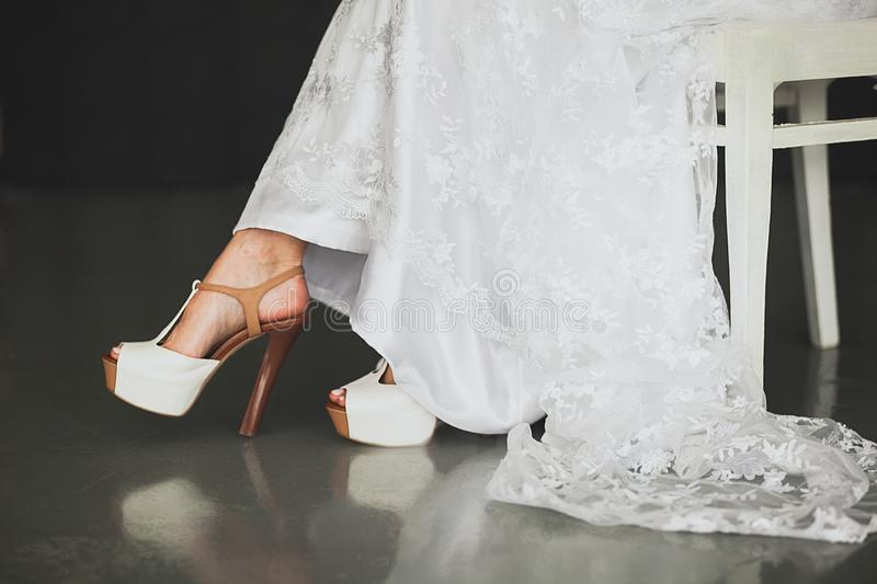 The bride, girl or young woman in a beautiful elegant modern stylish wedding dress and fashionable high-heeled shoes, sitting on a stock image