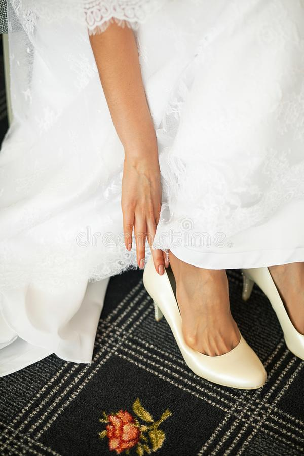 The bride, girl or young woman in an elegant modern stylish wedding white dress puts on leather fashionable cream high heel shoes royalty free stock image