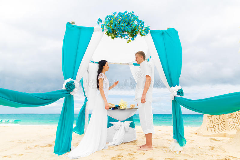 Bride giving an engagement ring to her groom under the arch decorated with flowers on the sandy beach. Wedding ceremony on. A tropical beach in blue. Wedding royalty free stock photography