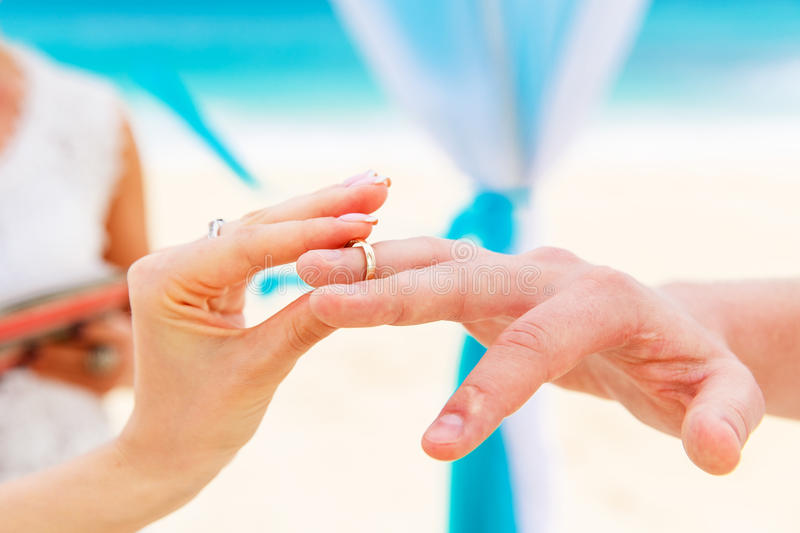 Bride giving an engagement ring to her groom under the arch decorated with flowers on the sandy beach. Wedding ceremony on. A tropical beach in blue. Wedding royalty free stock images