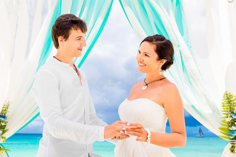 Bride giving an engagement ring to her groom under the arch decorated with flowers on the sandy beach. Wedding ceremony on. A tropical beach in blue. Wedding stock photos