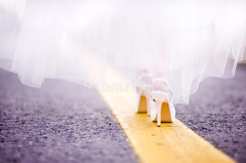 The bride goes along the yellow line along the road. Closeup of the legs of the bride in shoes. She goes exactly along the yellow line of the road marking along royalty free stock photography