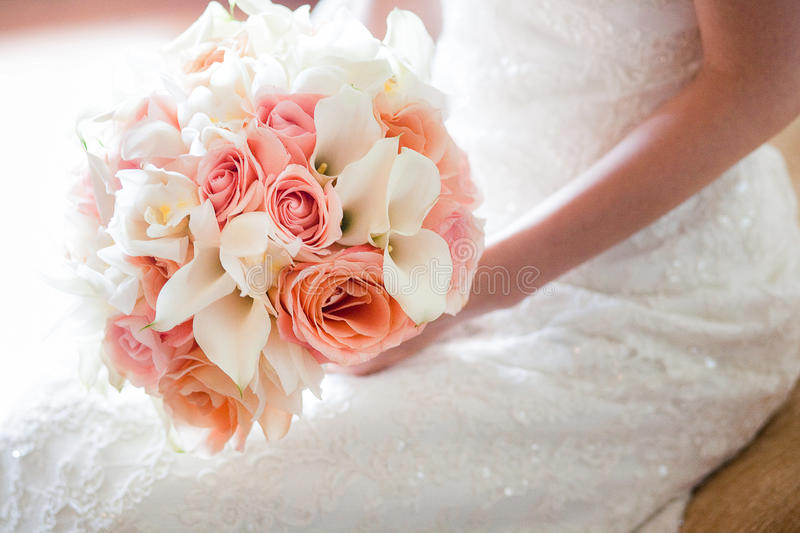 Bride with orange and pink wedding bouquet royalty free stock photography