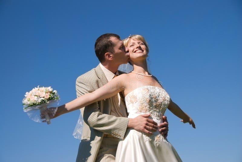 Bride and groom against blue sky. Happy bride and groom against blue sky royalty free stock photos
