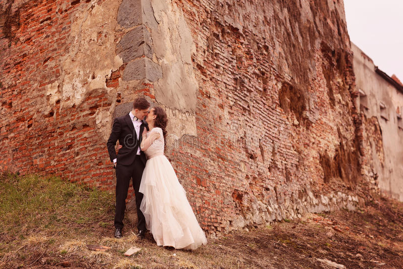 Bride and groom against a bricked wall stock images