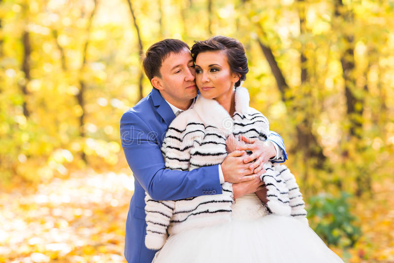 Bride and groom in autumn park. Autumn wedding royalty free stock photo