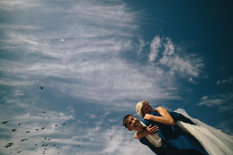 Bride and groom on the background of sky. Elegant stylish happy bride and gorgeous groom on the background of the sky stock photos