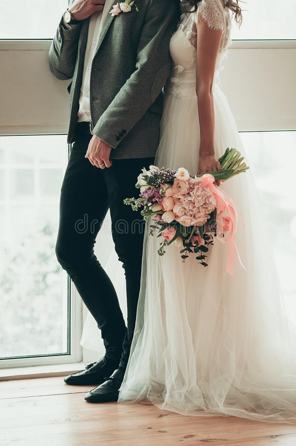Side view of Bride and Groom standing by the window royalty free stock images