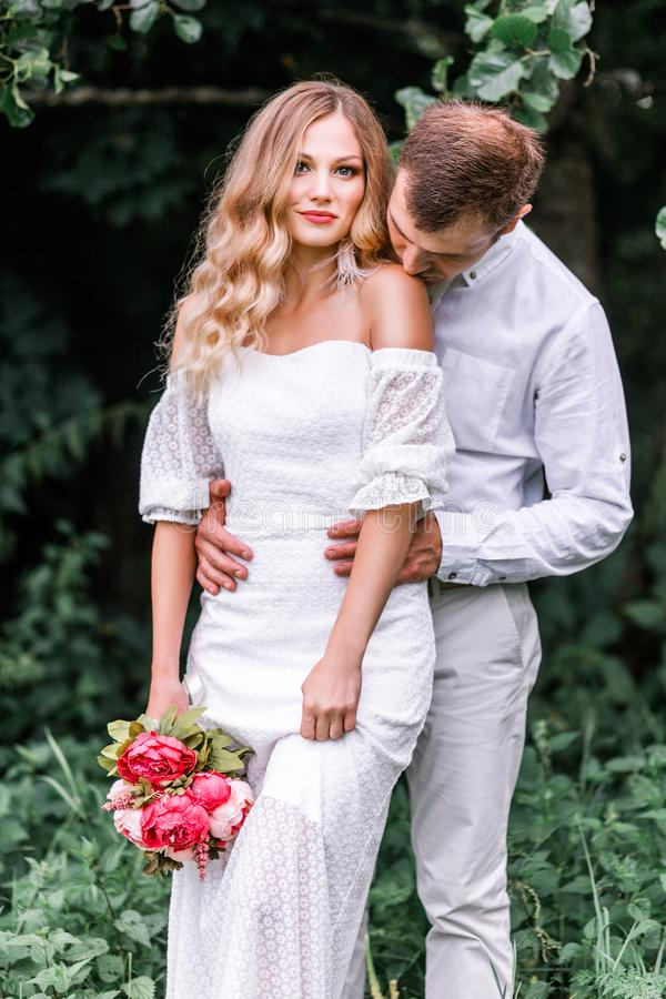 Bride and groom with a bouquet of peonies posing against the backdrop of the forest stock image