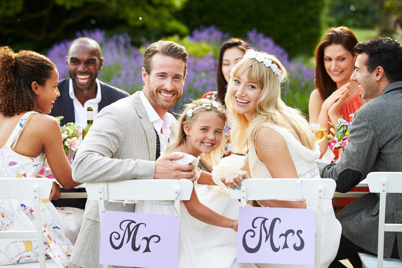 Bride And Groom With Bridesmaid At Wedding Reception. Sitting On Chair Outdoors Smiling To Camera stock images