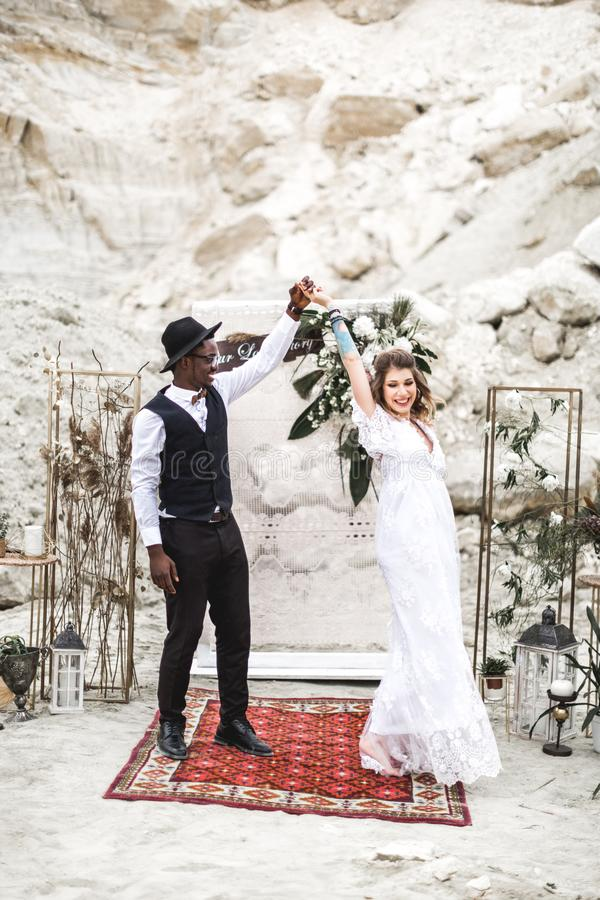 Bride and groom in canyon outdoors. wedding ceremony. boho wedding arch. African man and Caucasian woman in boho wear royalty free stock image
