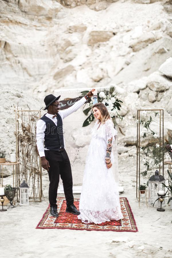 Bride and groom in canyon outdoors. wedding ceremony. boho wedding arch. African man and Caucasian woman in boho wear royalty free stock photos