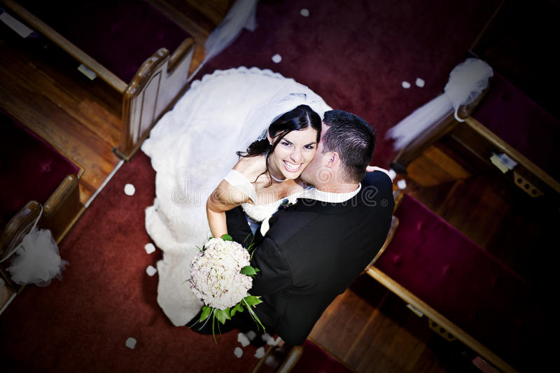 Bride and groom in a church. Groom kissing the neck of bride in the aisle of a church