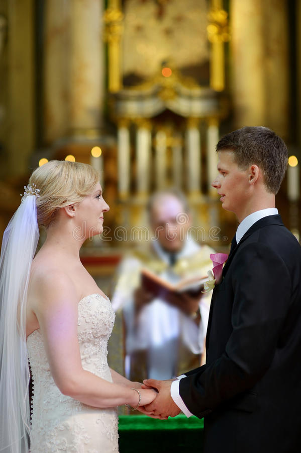 Bride and groom at the church. During a wedding ceremony royalty free stock image