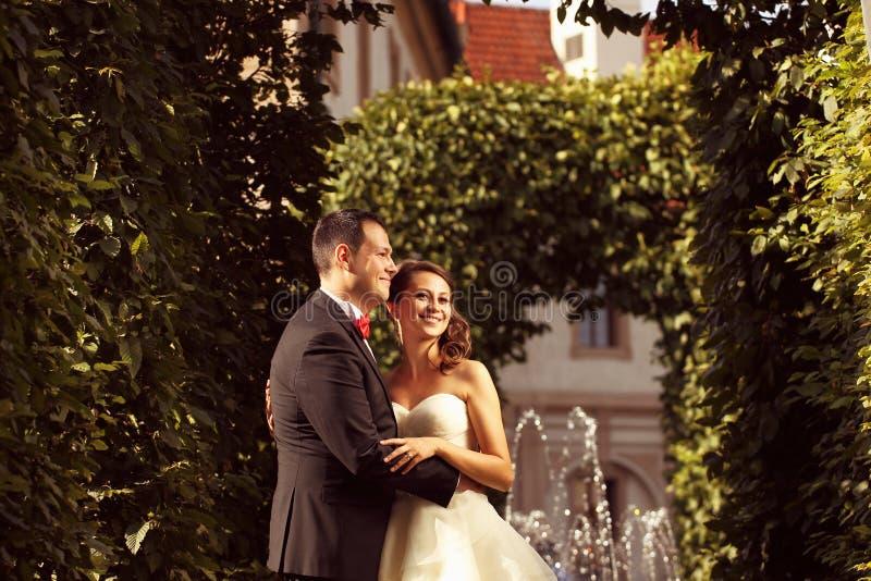 Bride and groom in the city. Happy bride and groom having fun garden city royalty free stock image
