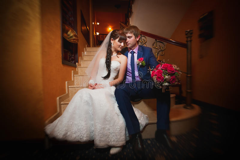 Bride and groom in the classic english interior. Bride and groom are hugging in the classic interior
