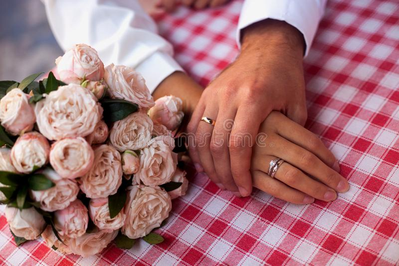 Bride and groom close up of hands with rings and wedding bunch of flowers stock photos