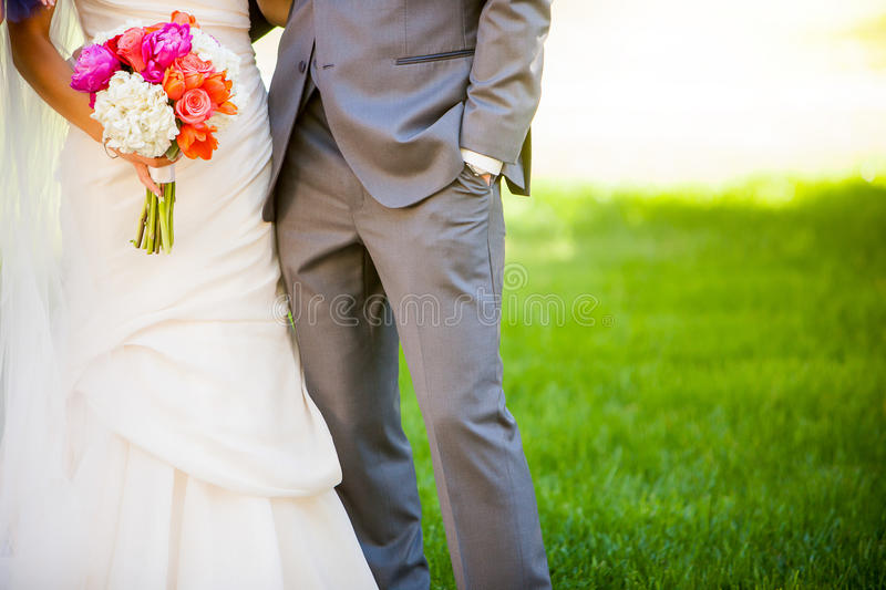 Bride and Groom. Closeup of Bride and Groom holding hands at a wedding. Bride is holding colorful beautiful wedding bouquet royalty free stock images
