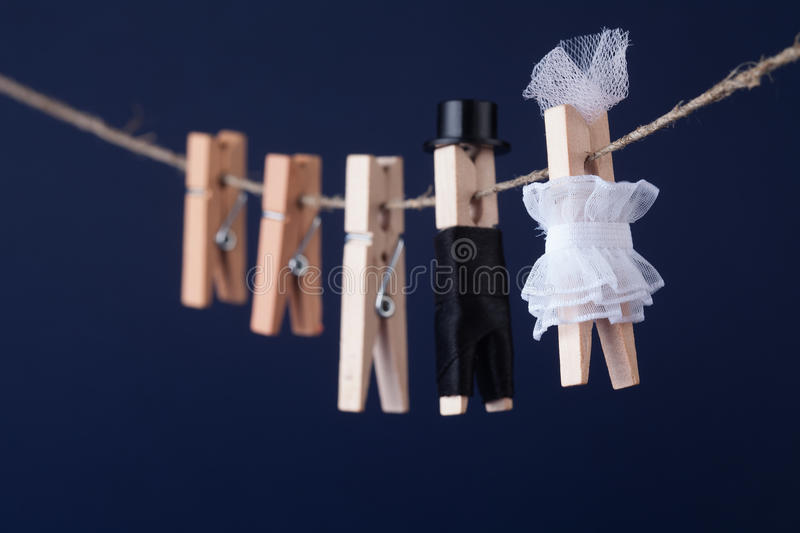 Bride and groom clothespin toys, clothesline. Abstract woman in white dress man character with black suit hat. Love royalty free stock images