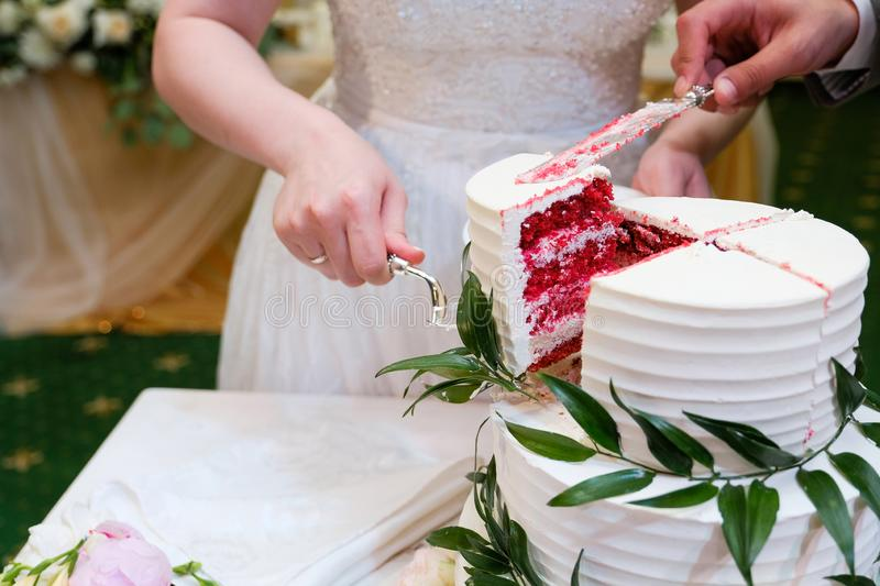 The bride and groom cut an elegant three-tiered white wedding cake decorated with natural flowers or roses and green leaves on a royalty free stock images