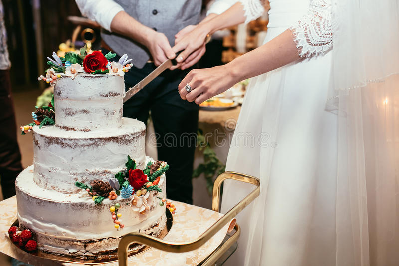 Bride and groom cut rustic wedding cake on wedding banquet with stock images