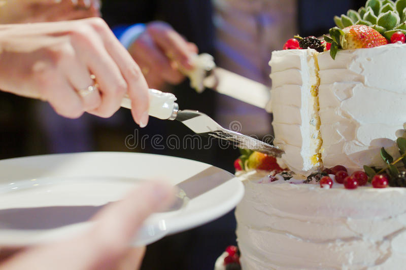 Bride and groom cut wedding cake stock photo