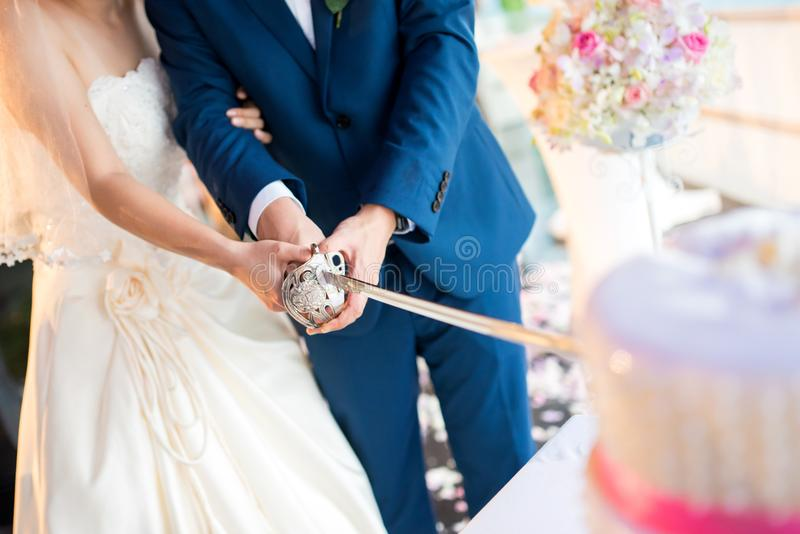 Bride and groom cutting the cake at a wedding ceremony. royalty free stock image
