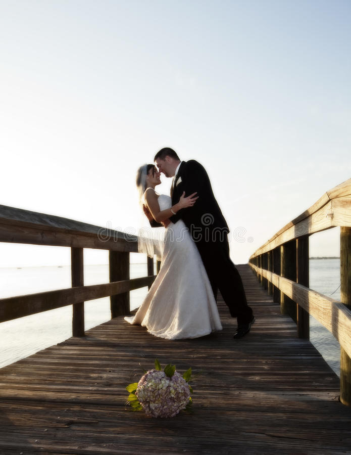 Bride and Groom dance. A bride and groom dancing on a boardwalk outdoors. Floral bouquet on the ground