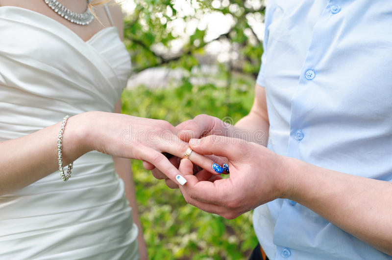 Bride groom dresses a wedding ring on her finger royalty free stock photography