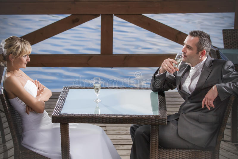 The bride and groom drinking champagne stock image